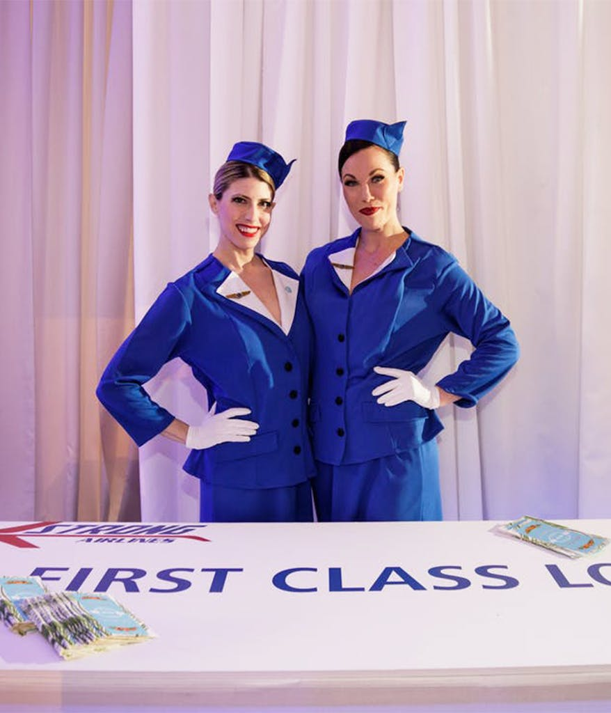 ladies dressed up as flight attendants in front of a pretend first class lounge at a travel themed birthday party in Chicago
