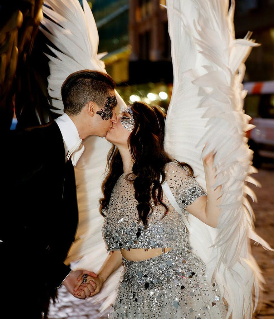 bride and groom kissing in costume at their themed wedding wearing masks and wings