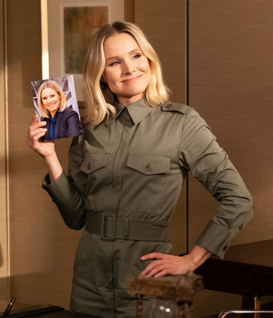 Kristin Bell wearing a green jumpsuit holding up a photo on The Good Place