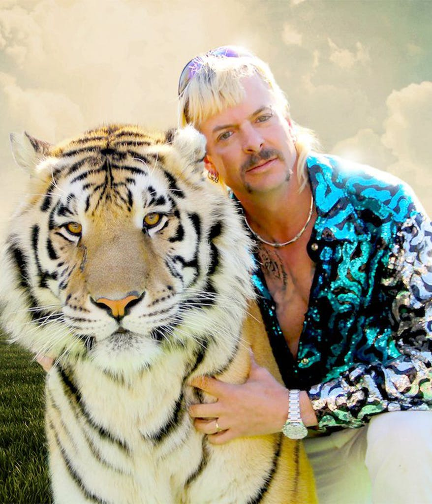 Joe Exotic from Netflix's Tiger King posing with a large Tiger