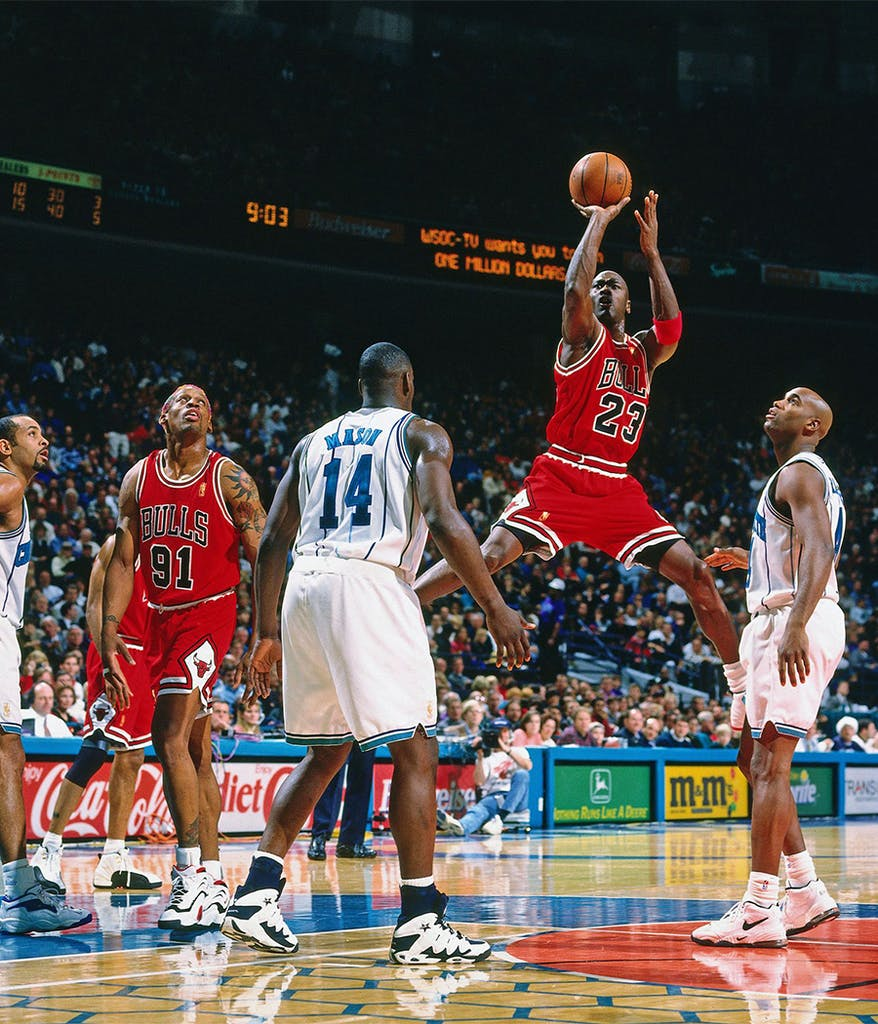 Michael Jordan in the air shooting the basketball during a game as he plays for the Chicago Bulls