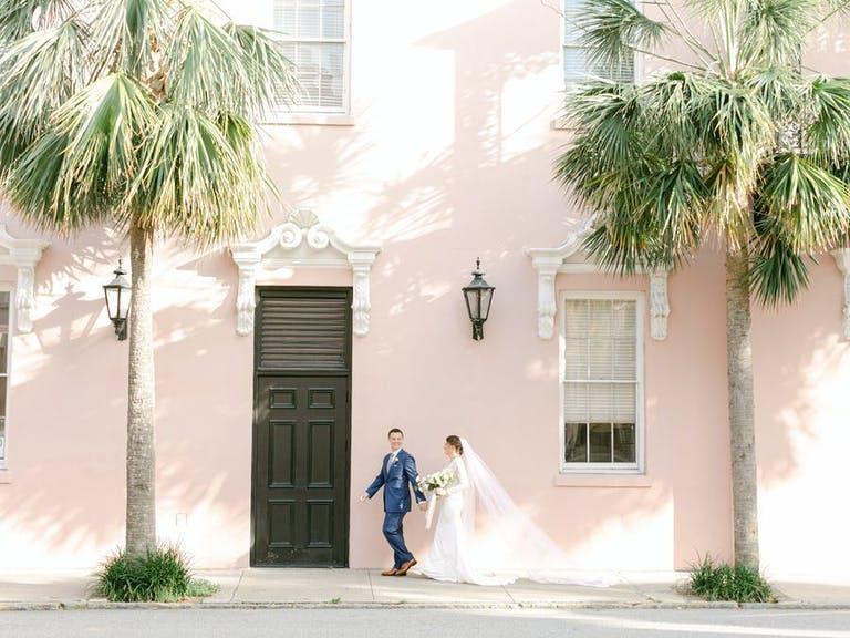 Micro wedding photo shoot with light pink wall background and palm trees   PartySlate