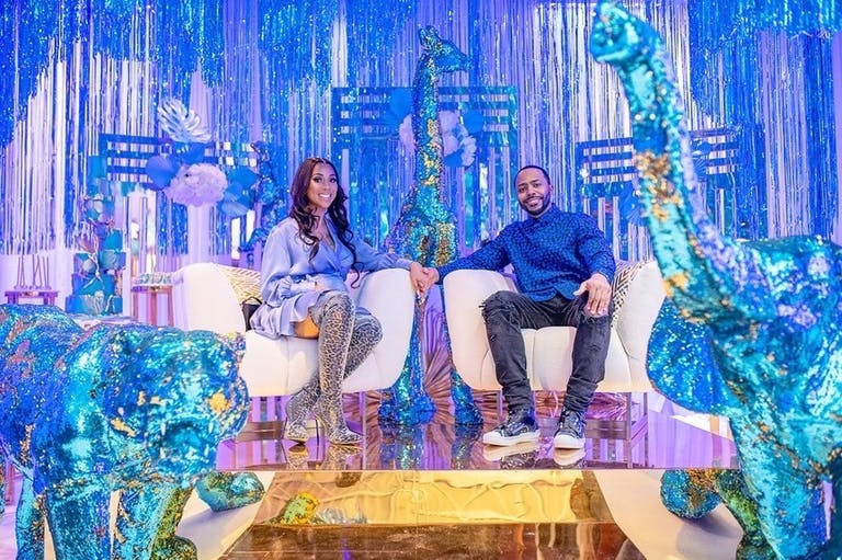 Parents-to-Be Sit on White Chairs Against Iridescent Backdrop and Glittery Blue Animal Sculptures   PartySlate