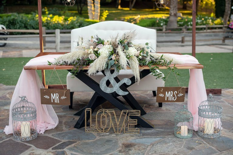 Sweetheart Table With Rustic Wedding Centerpieces Featuring Pampas Grass and Pink Drapery | PartySlate