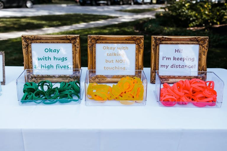 Three different colored wristbands to notion your comfortable levels at a micro wedding   PartySlate