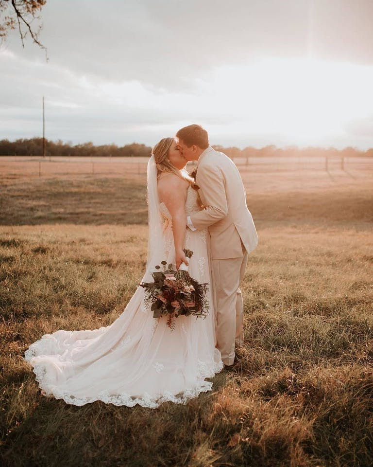 Bride and Groom Kiss at The Texana Grounds at The Grand Texana, a Wedding Venue in Houston | PartySlate