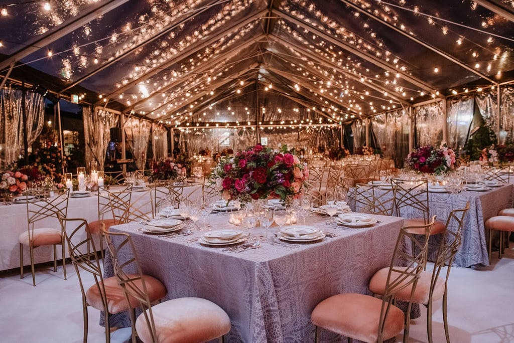 Clear Wedding Tent With String Fairy Lights, Pink Seating, and Pink Flower Centerpieces | PartySlate