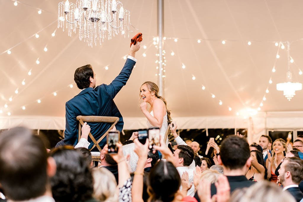 Hora in Pole Wedding Tent With String Lights and Chandeliers | PartySlate