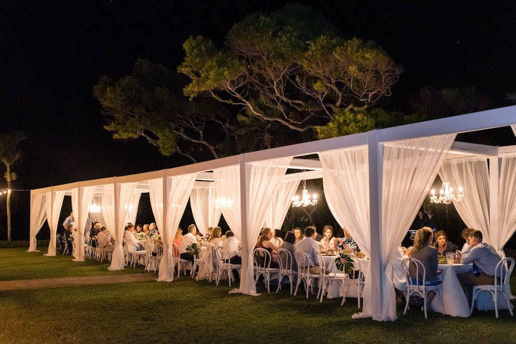 Long Cabana Wedding Tent With White Drapery Illuminated by Chandeliers | PartySlate