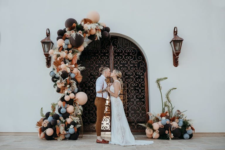 A micro wedding with beautiful balloon installation with pinks and dark colors   PartySlate