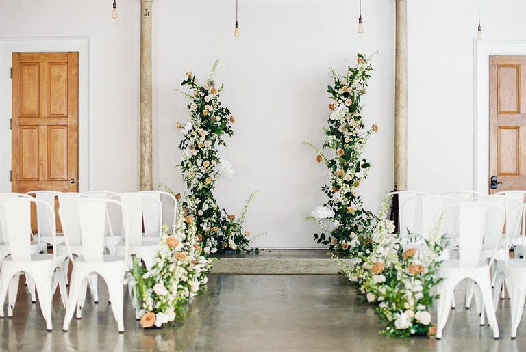 Monochrome micro wedding with white walls and chairs and greenery   PartySlate