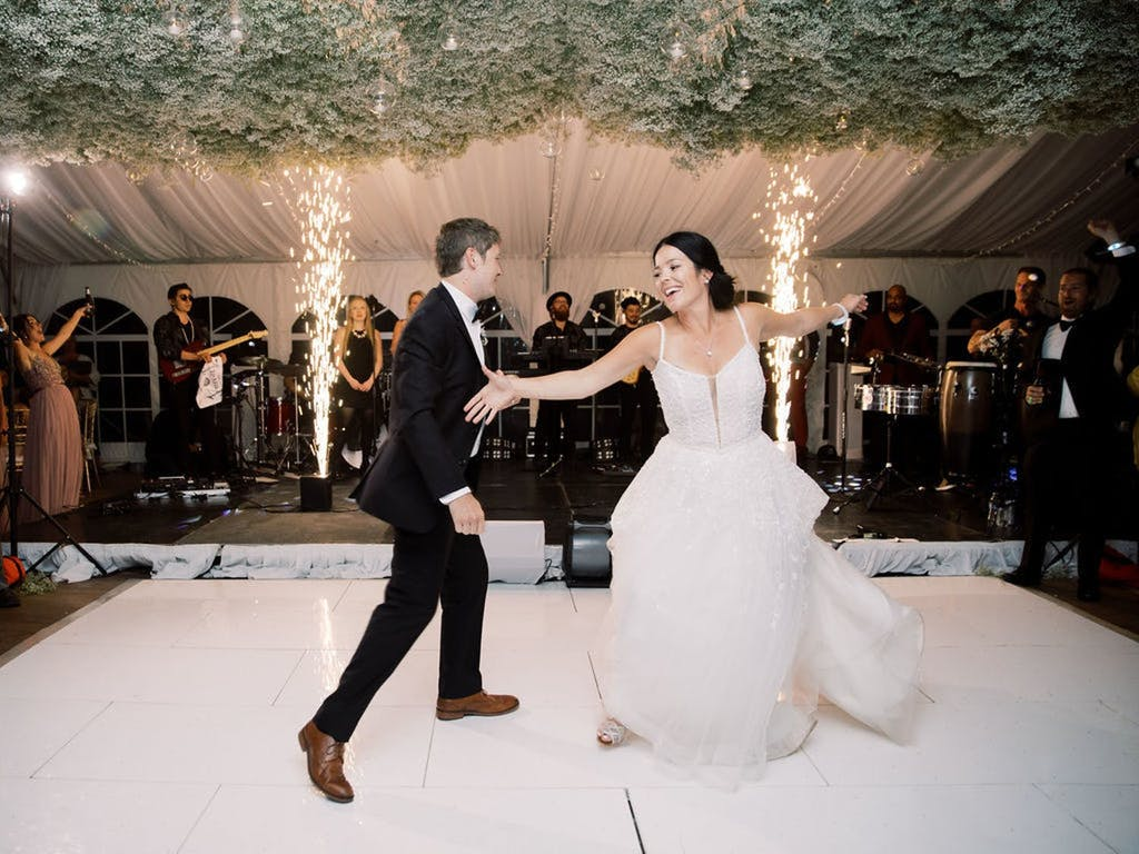 Couple Dance in White Wedding Tent With Baby's Breath Ceiling installation | PartySlate
