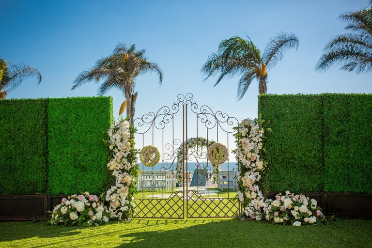 Beautiful gates leading to an outdoor beach wedding venue space | PartySlate