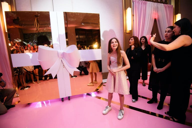 Interactive Dessert Station Behind Two Gold Doors Wrapped in a Pink Bow at Pink-Themed Bat Mitzvah Party | PartySlate
