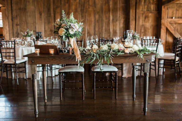 Rustic Wedding Centerpieces With Greenery, Peach Ribbon, and a Vintage Camera | PartySlate