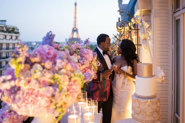 Balcony image of bride and groom with a view of the Eiffel Tower   PartySlate