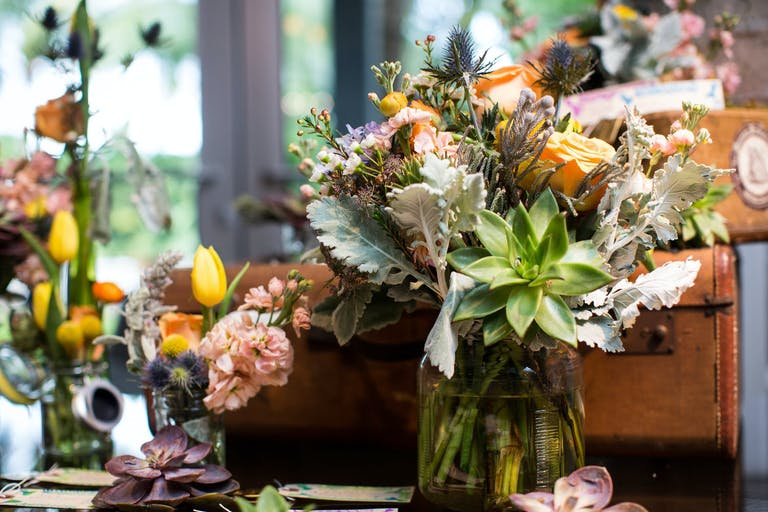 Bright Floral Wedding Centerpieces With Succulents and Rustic Suitcases | PartySlate
