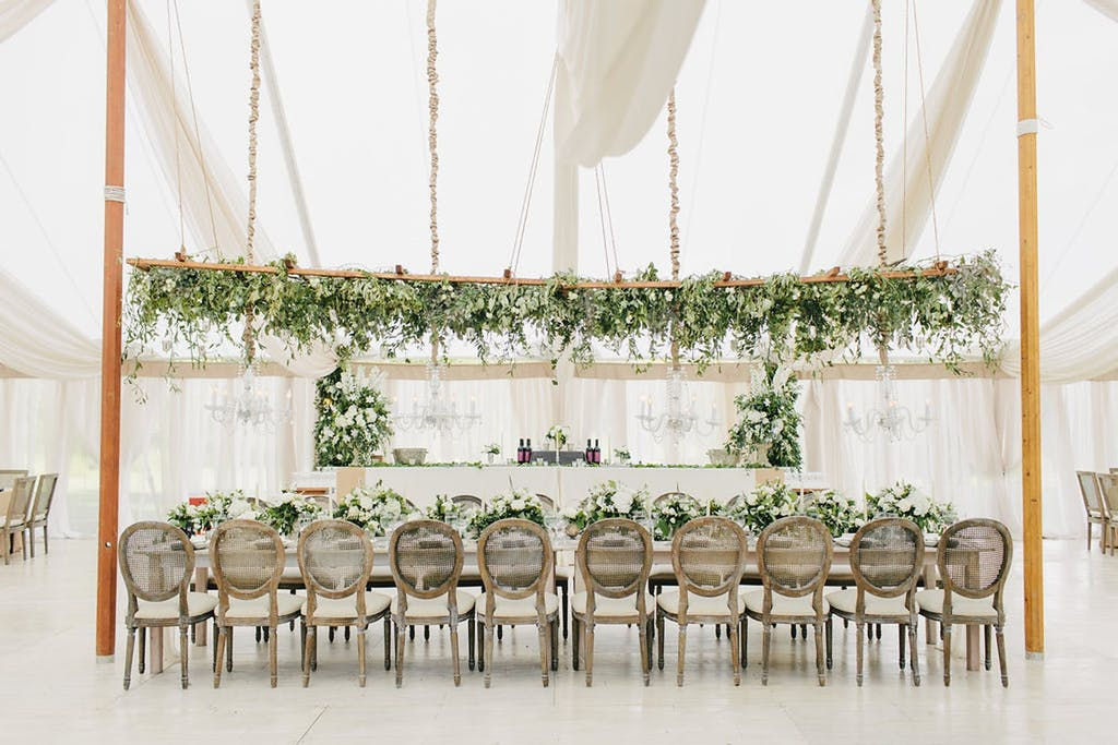 Ethereal White Canopy Wedding Tent With Elevated Greenery Centerpieces | PartySlate