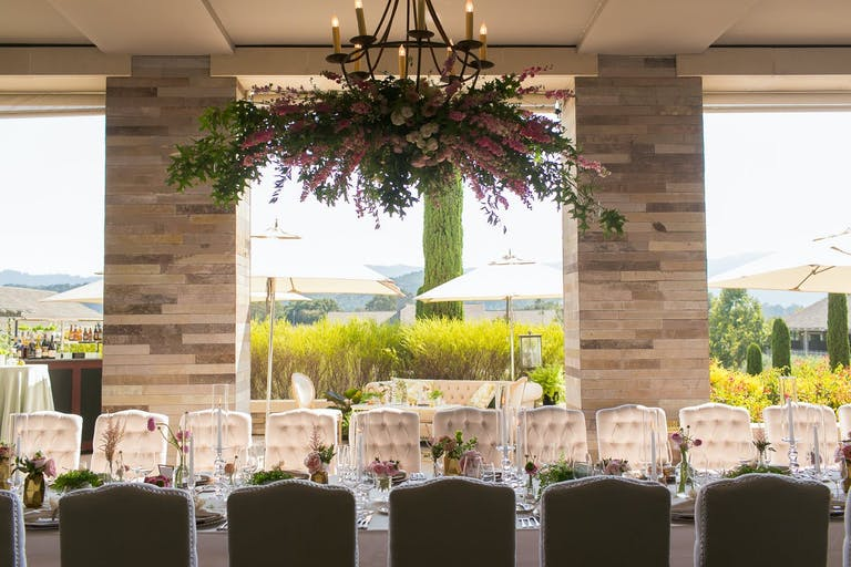 Sophisticated micro wedding with floral arrangement hanging above the dining table   PartySlate