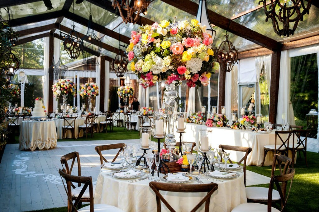 Clear Wedding Tent With Rustic Wooden Beams and Colorful Floral Centerpieces | PartySlate