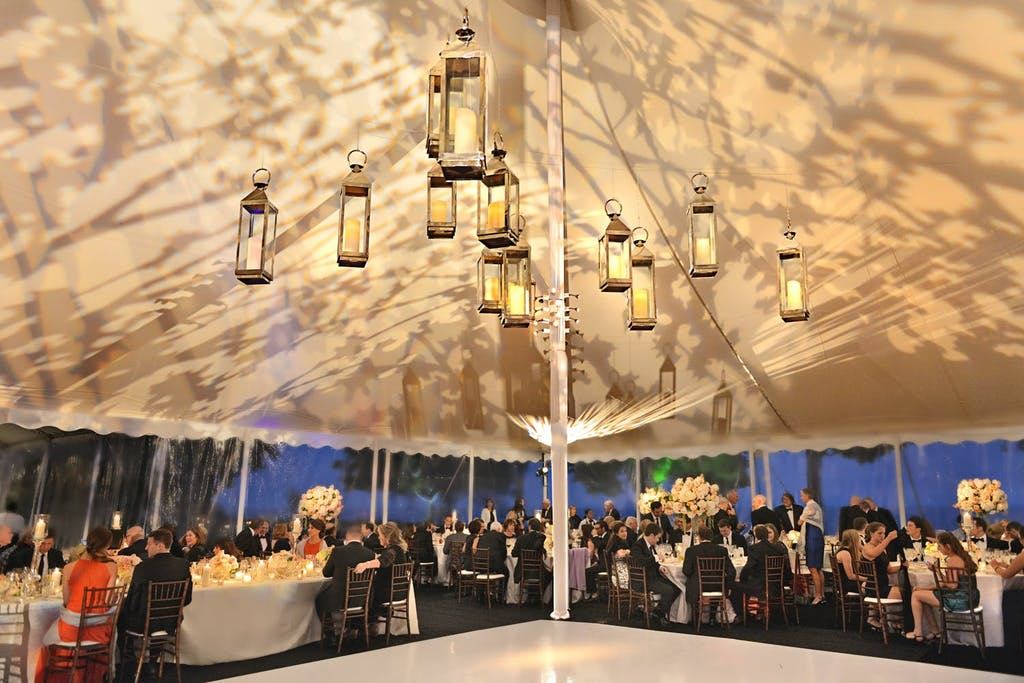 White Pole Wedding Tent with Lantern Ceiling Installation and Shadowy Leaf-Patterned Roof | PartySlate