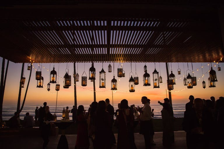 Beautiful California beach wedding with lanterns as decor | PartySlate