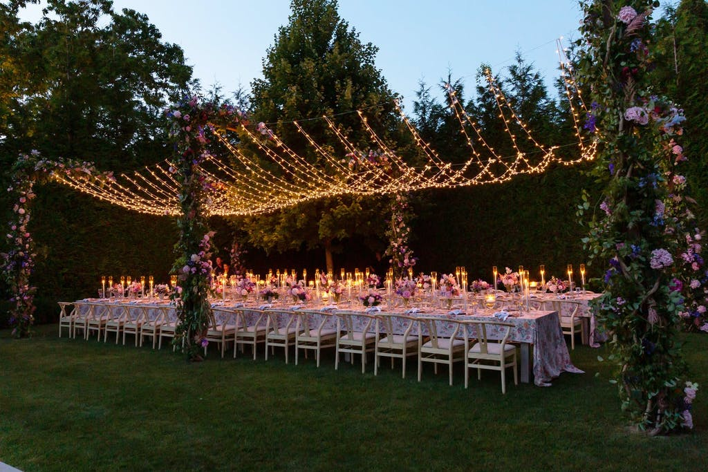 String Light Wedding Tent Structure With Floral Pillars | PartySlate