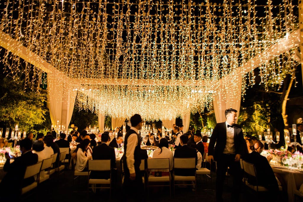 Outdoor Nighttime Wedding Reception with Open Tent Structure With String Lights | PartySlate