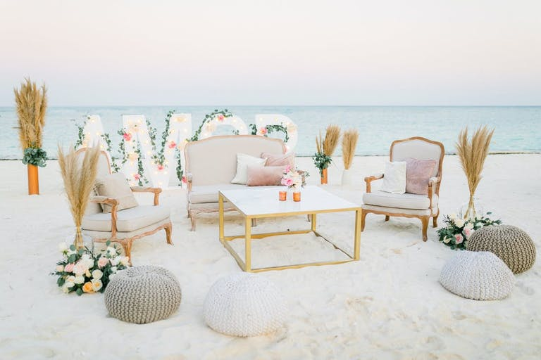 Amor floral sign on the beach with furniture seating | PartySlate