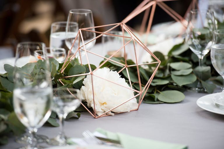 Rustic Wedding Centerpieces With Greenery Garland and Copper Geometric Structures | PartySlate