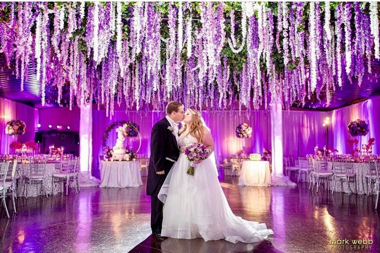 Couple Kiss Under Purple Floral Wedding Ceiling Installation Designed by The Style Marc | PartySlate