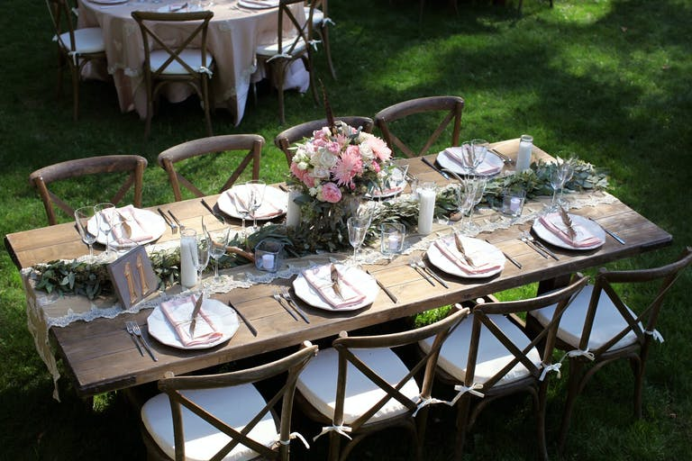 Rustic Wedding Tablescape With Pink Floral Centerpieces and Greenery Garland | PartySlate