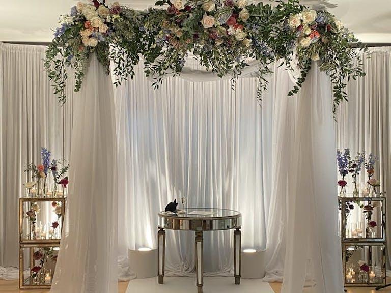 White linen backdrop with enchanting floral arrangements   PartySlate
