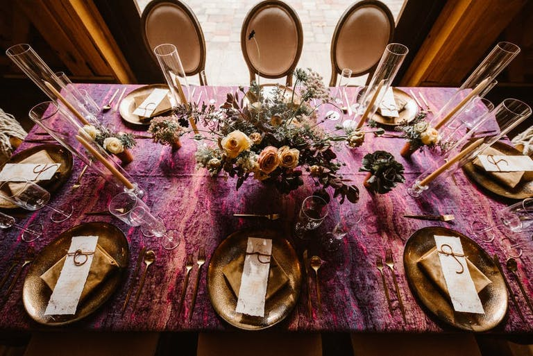 Rustic purple table cloth at a micro wedding with beautiful florals and gold vintage detail   PartySlate