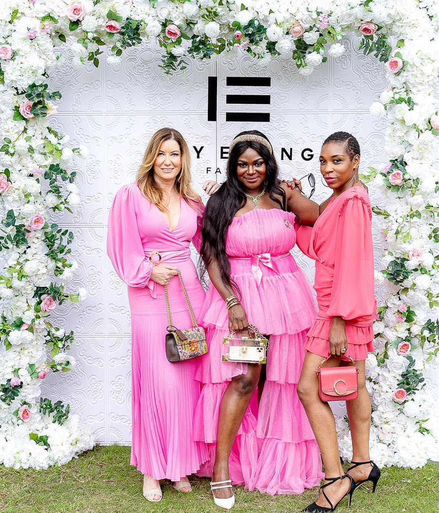 3 women in pink dresses standing in front of a branded photo op at a charity event