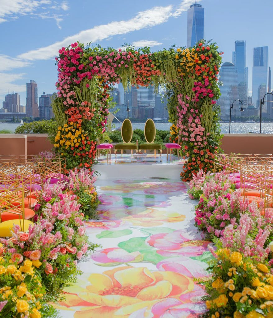 an Indian wedding ceremony with ombre flowers lining an aisle covered in flower drawings