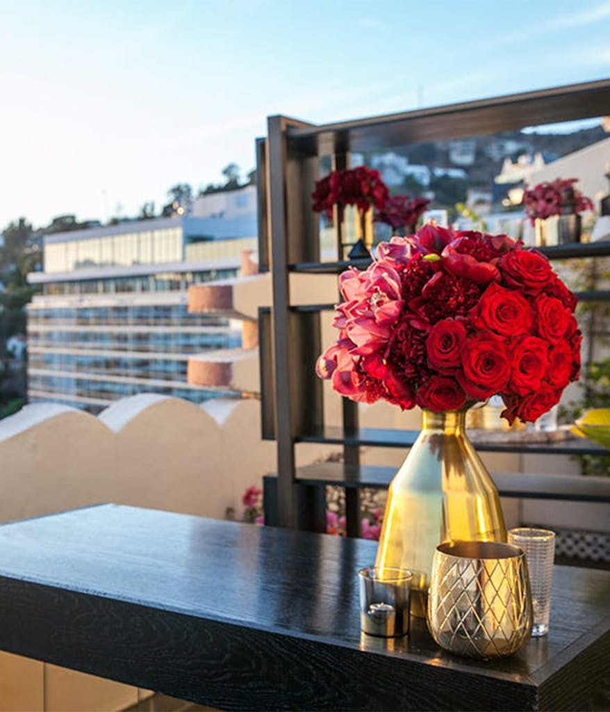a rooftop birthday party in LA with a black bar, red roses, and gold vases