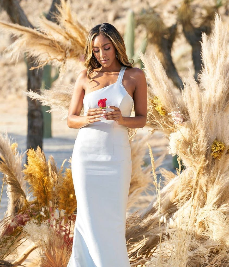 Tayshia from the Bachelorette in front of pampas grass wearing a white dress and holding her final rose