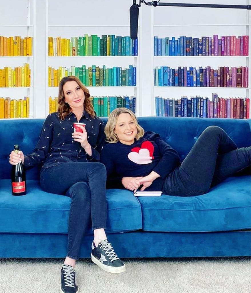 Clea and Joanna from the Home Edit on a blue couch in front of a rainbow organized book shelf
