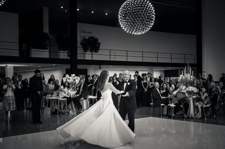 Black and White Photo of Bride Dancing With Father Beneath a Globed Geometric Chandelier | PartySlate