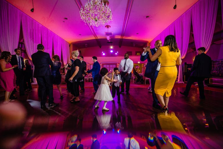 Friend and Family Dance on Mirrored Wedding Dance Floor Amidst Hot Pink Uplighting | PartySlate