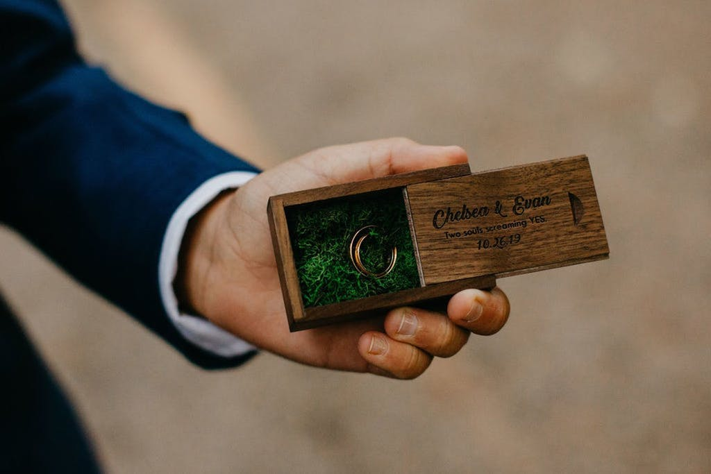 Man in Blue Tux Hold Wedding Ring in Wooden Engraved Box with Bed of Moss | PartySlate