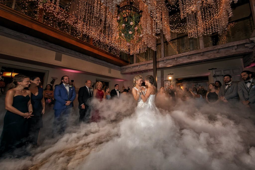 Enchanted Forest Theme Wedding With Two Brides Dancing Through Fog Machine on DanceFloor | PartySlate