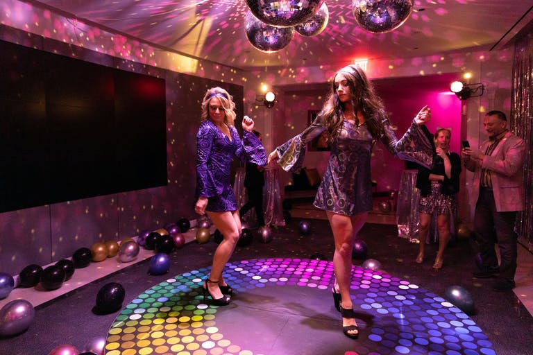 Two Girls in Disco Clothes Dance on a Rainbow Circular Stage With Disco Balls Overhead | PartySlate