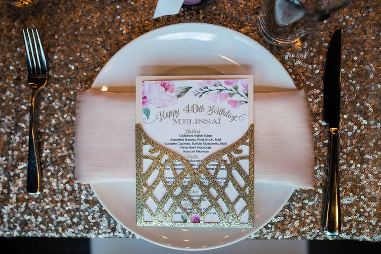 40th-Birthday Party Table Setting With Light Pink Napkin and Glittering Gold Menu | PartySlate
