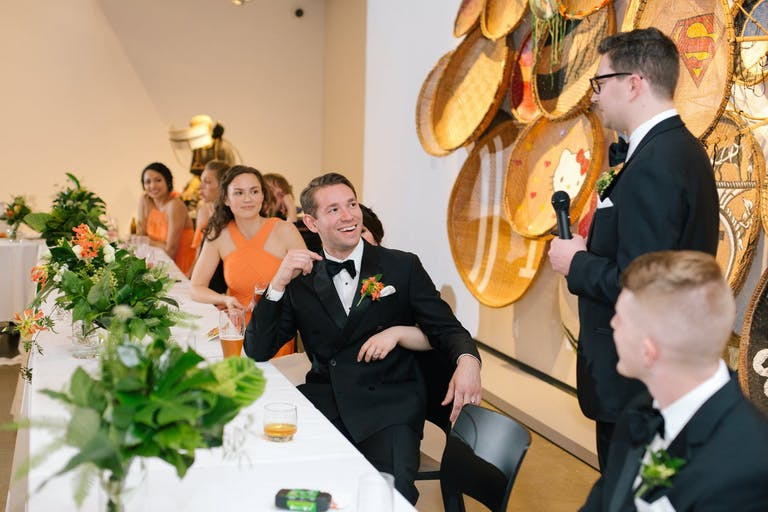 Wedding Party Reception Table at Contemporary Museum. Bridesmaids Wear Orange to Match the Orange-Accented Greenery Centerpieces | PartySlate