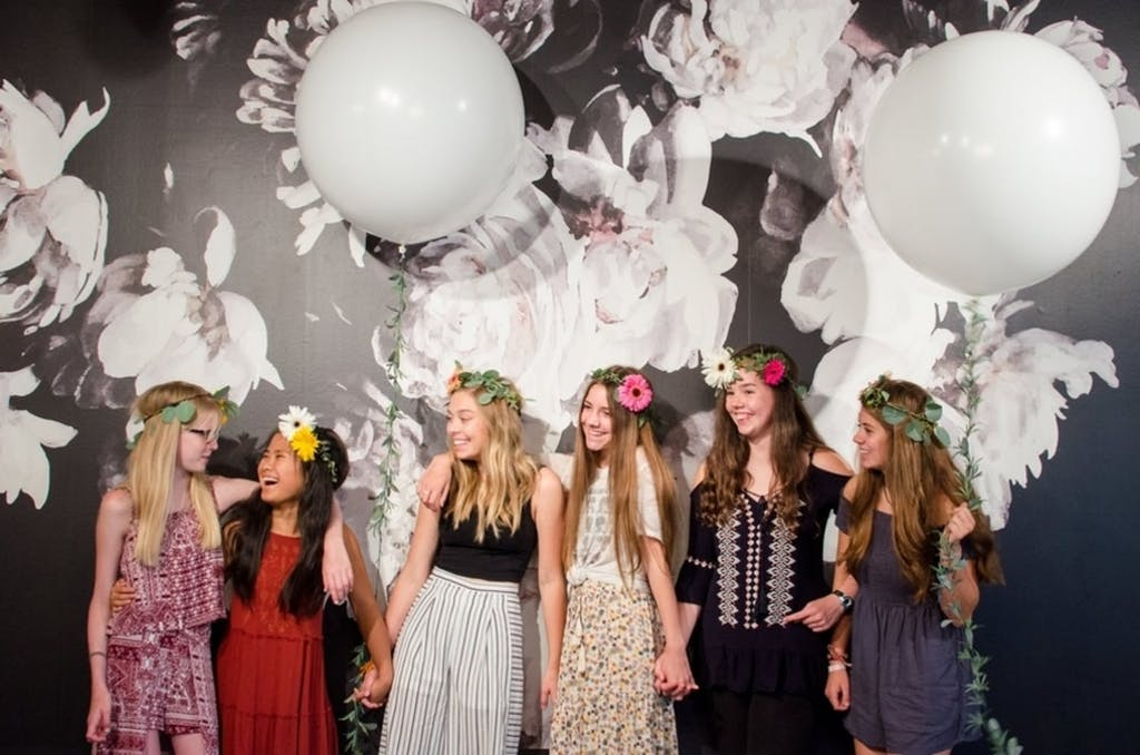 Six Girls Pose in Front of Black and White Floral Backdrop With White Balloons | PartySlate