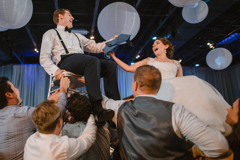 Wedding Hora With Bride and Groom Lifted into the Air Underneath White Globed Paper Lanterns | Partyslate