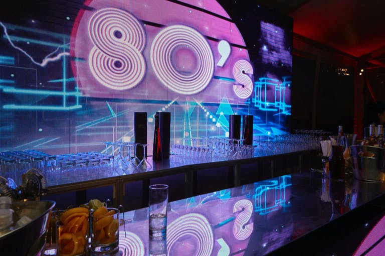 80s Theme Party Bar With PInk and Blue Lighting | PartySlate