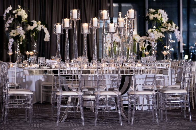 Wedding Tablescape With Lucite Seating and Towering Glass Candleholders | PartySlate